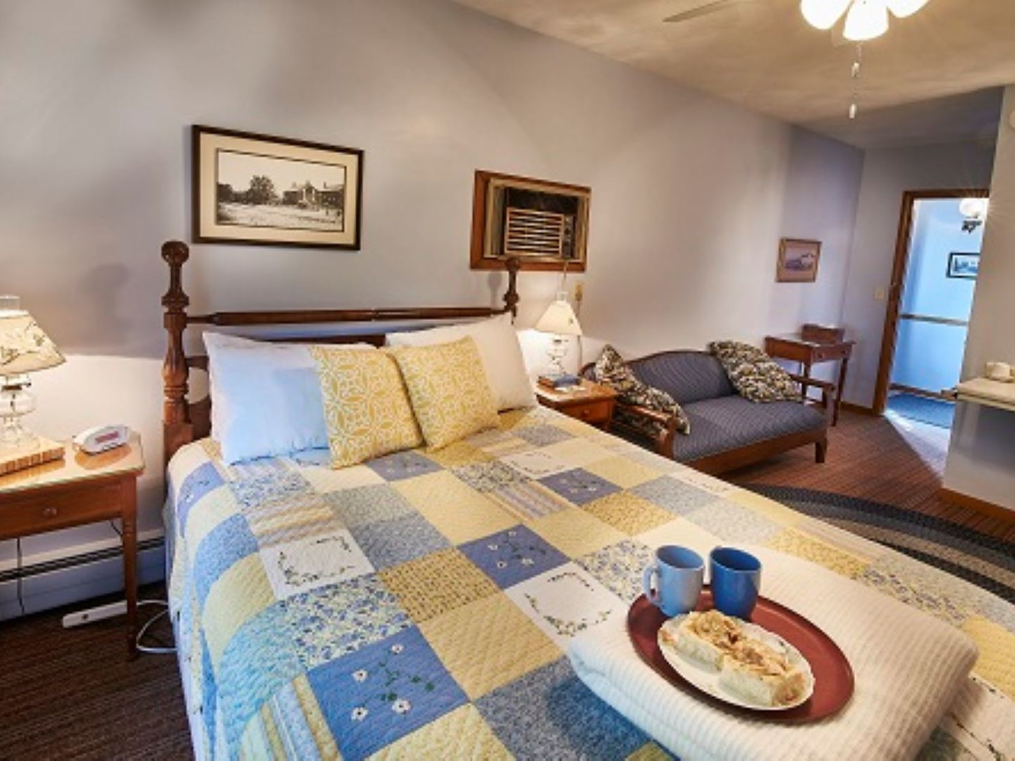 A bedroom with a bed and desk in a room at Die Heimat Country Inn.