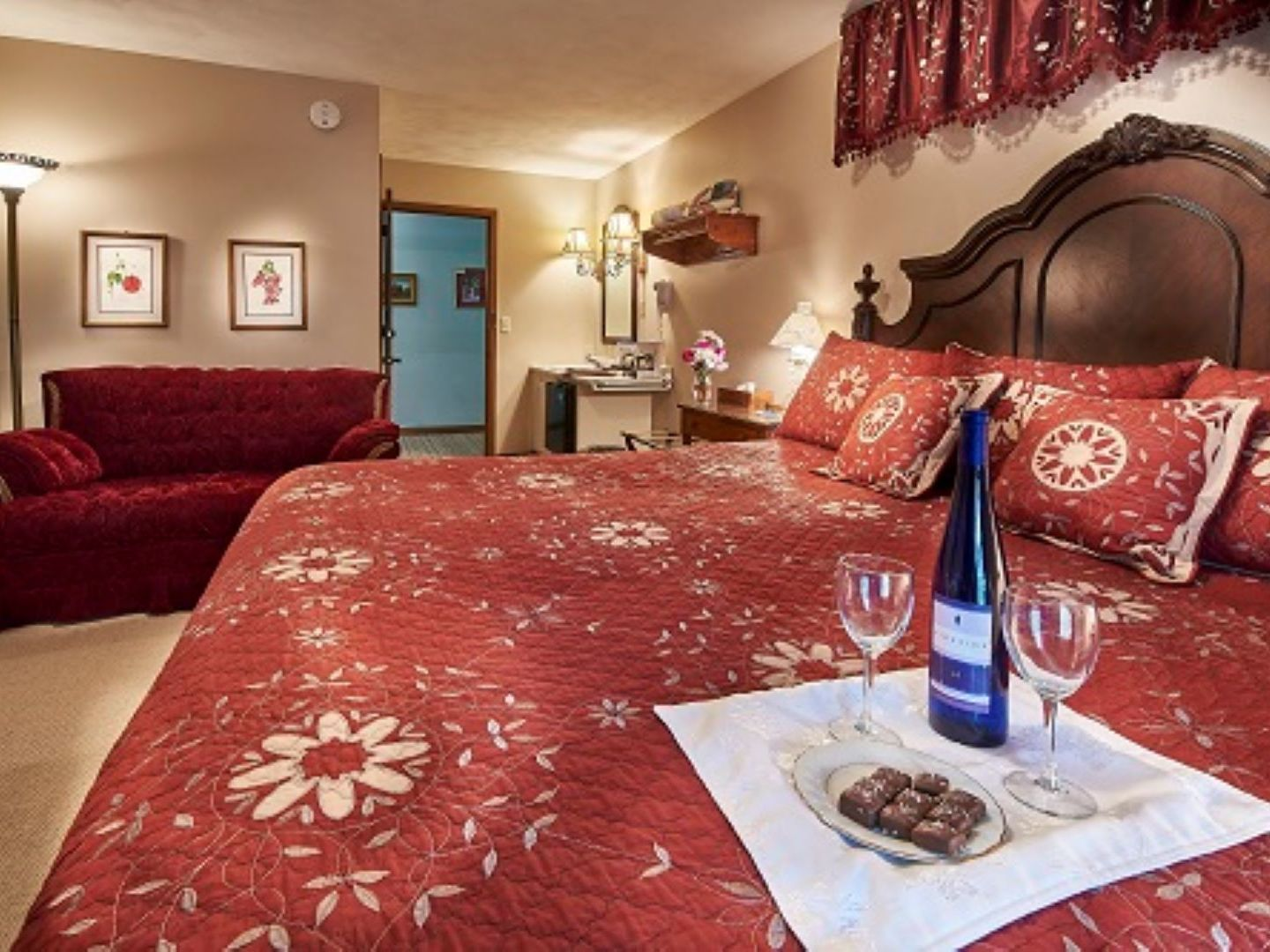 A bedroom with a glass of red wine on a table at Die Heimat Country Inn.