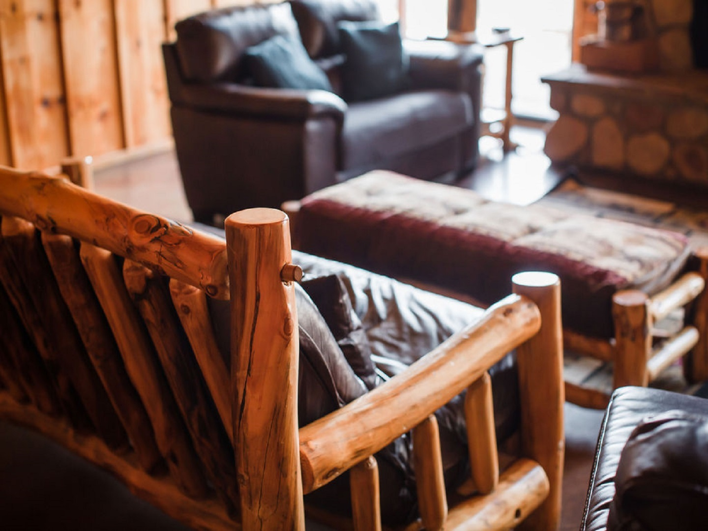 A living room with a leather chair at Three Falls Cove.