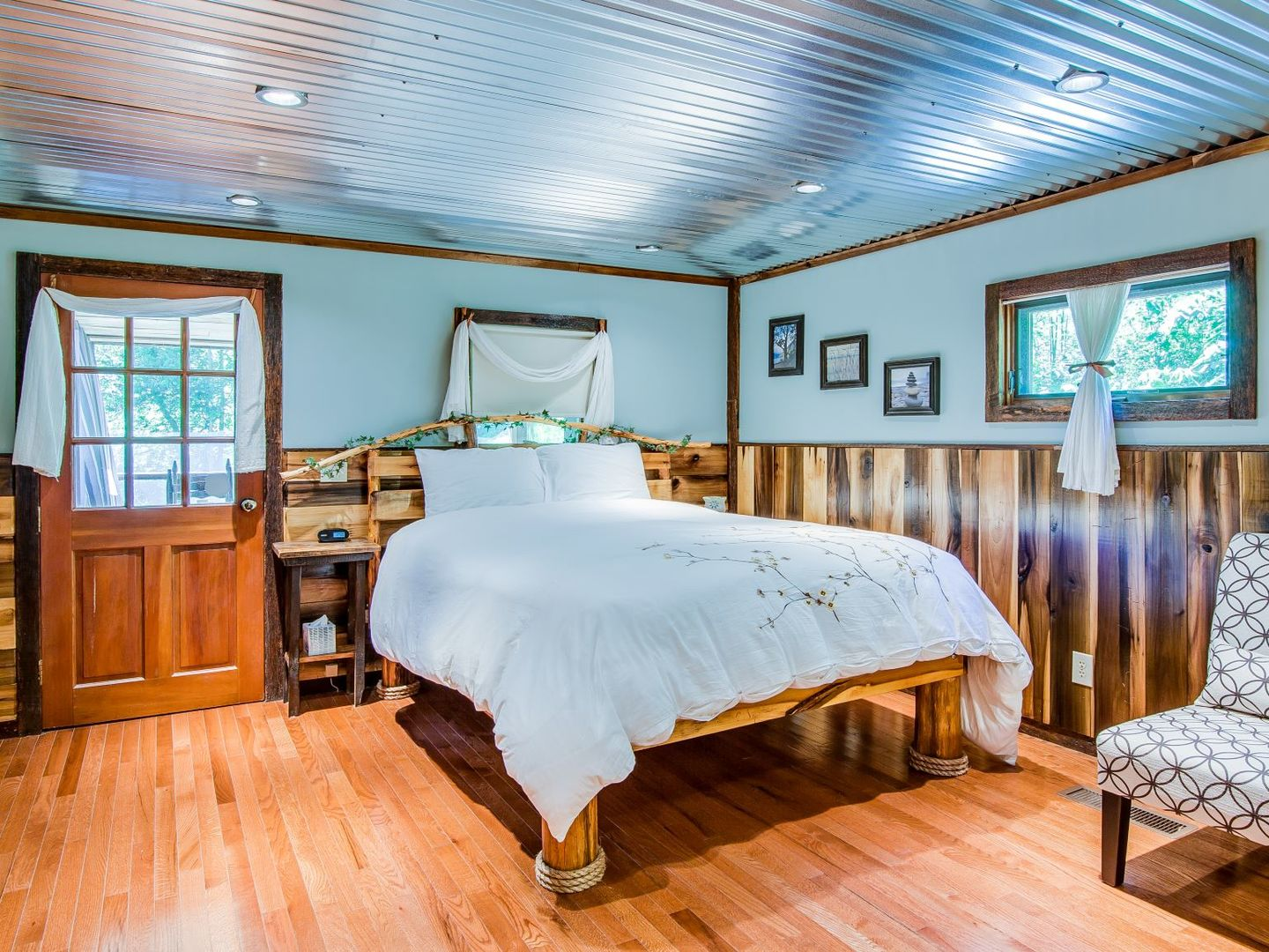 A bedroom with a bed and a chair in a room at Butterfly Hollow Bed and Breakfast.