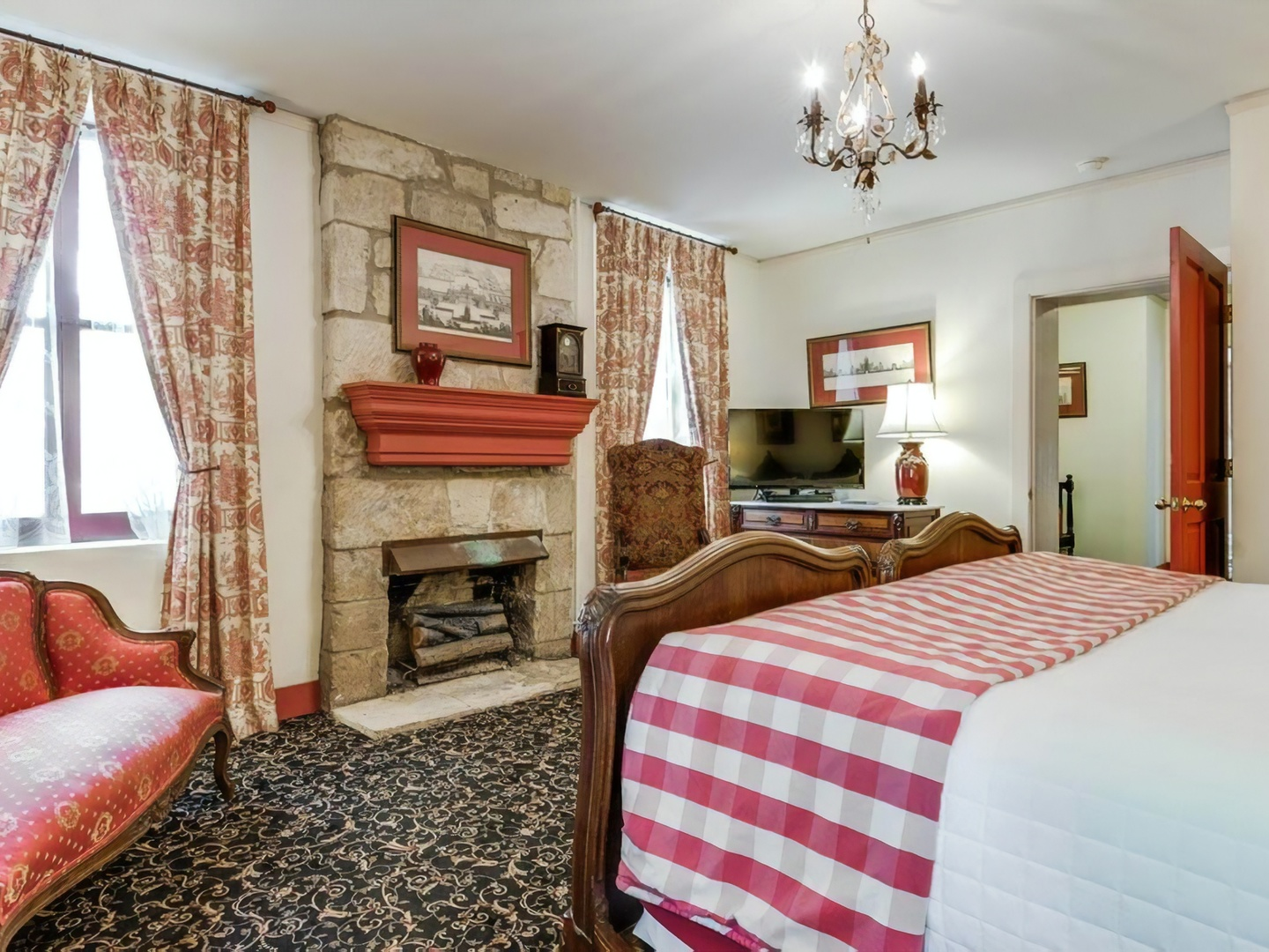 A bedroom with a large red chair in the living room at Noble Inns.