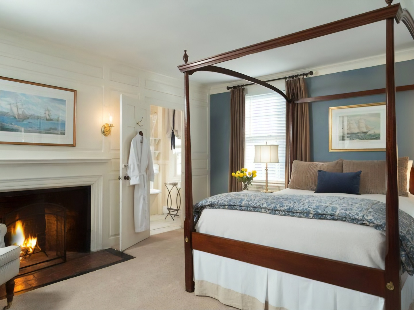 A bedroom with a bed and a fireplace at Harbor Light Inn.