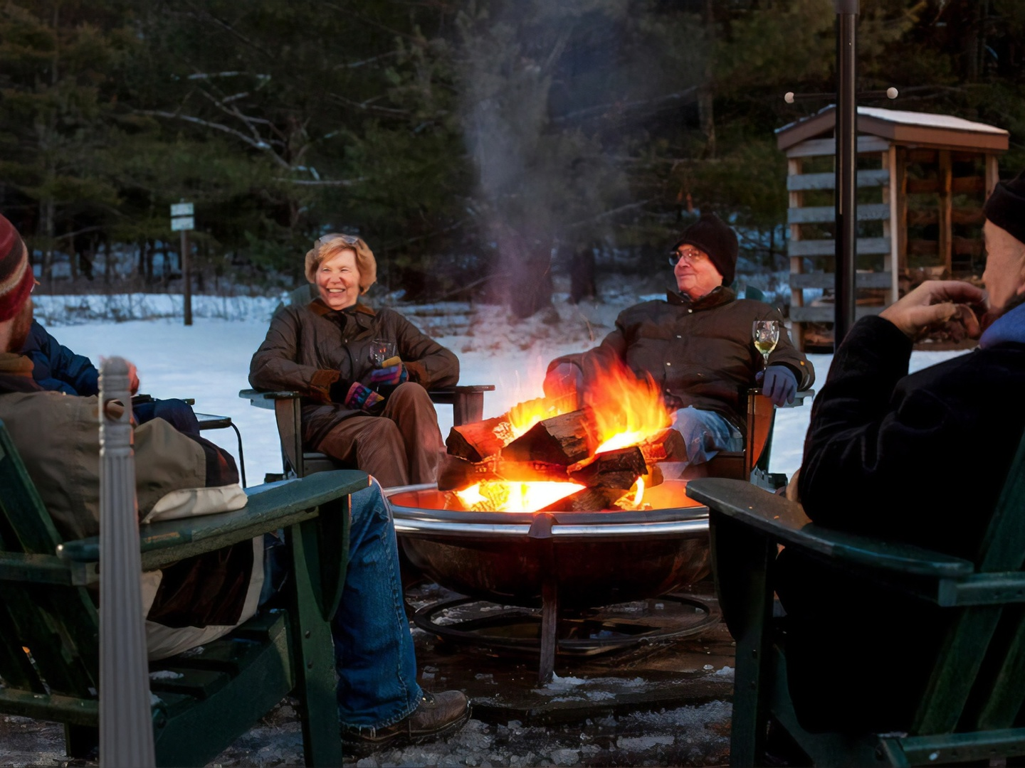 A group of people sitting around a fire at Inn at Lake Joseph.