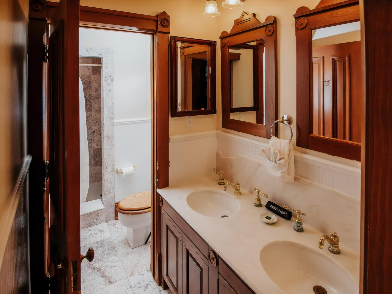 A white sink sitting under a mirror at Inn at Pine Terrace.