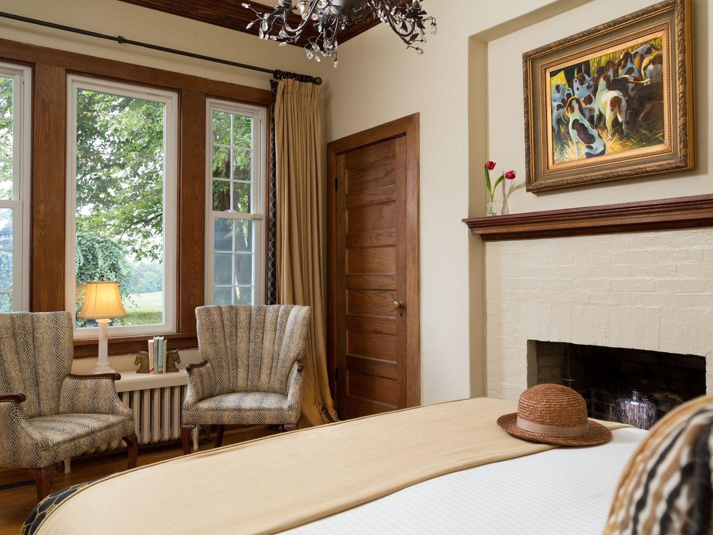 A bedroom with a fireplace and a large window at Glen Gordon Manor .