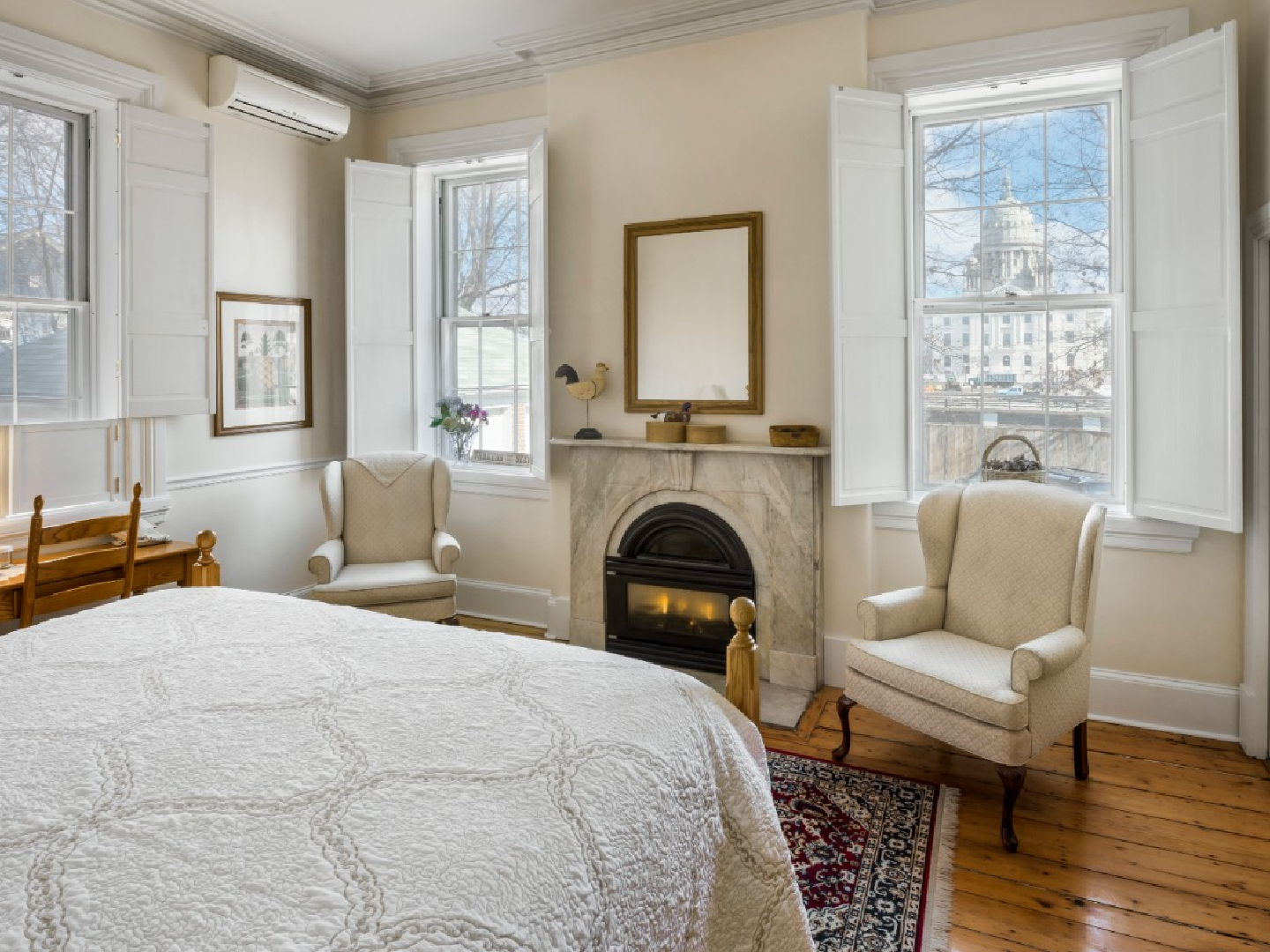 A bedroom with a fireplace and a large window at Christopher Dodge House.