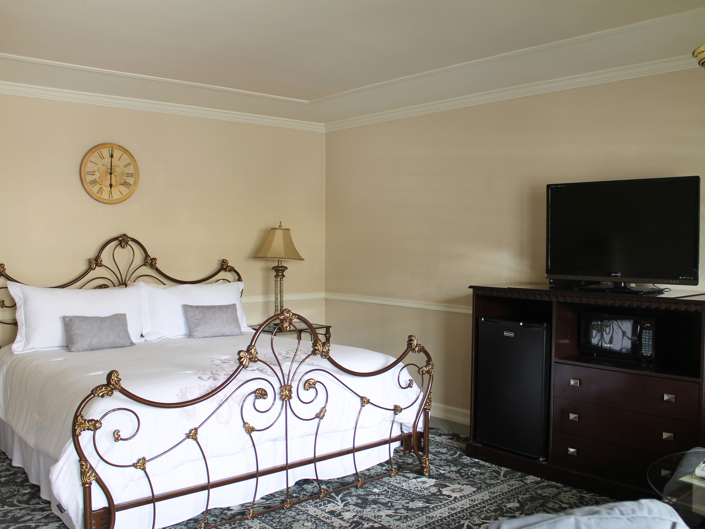 A bedroom with a bed and desk in a room at Coachman's Inn,  A Four Sisters Inn.