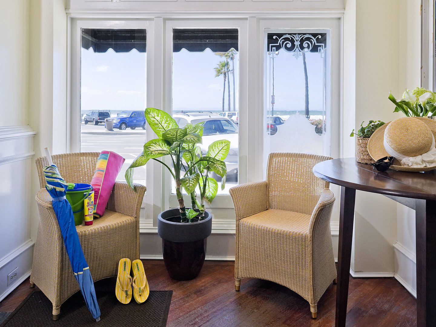 A room filled with furniture and vase of flowers on a table at Newport Beach Hotel, A Four Sisters Inn.