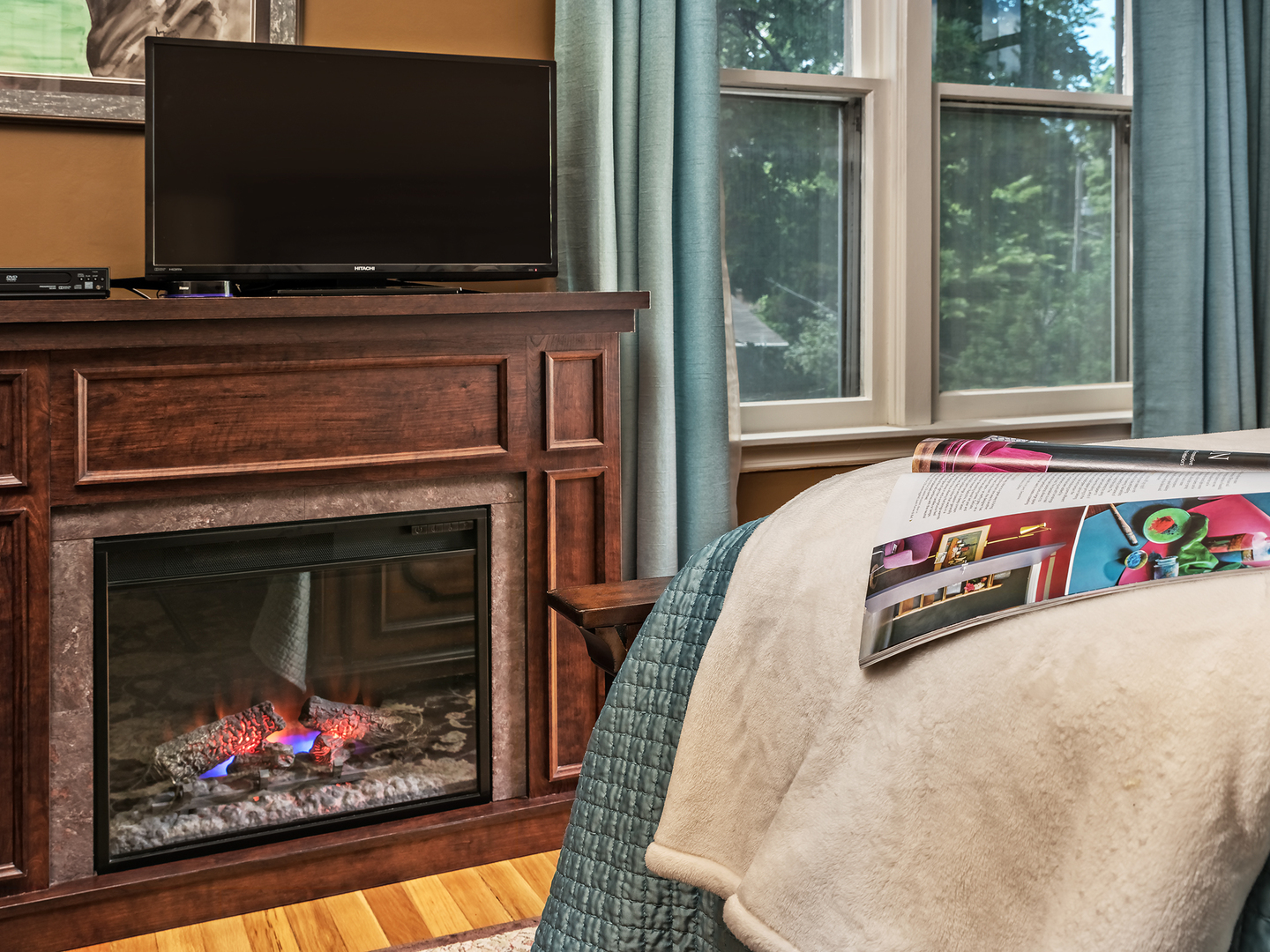 A fire place sitting in a living room with a fireplace at Silver Heart Inn & Cottages.