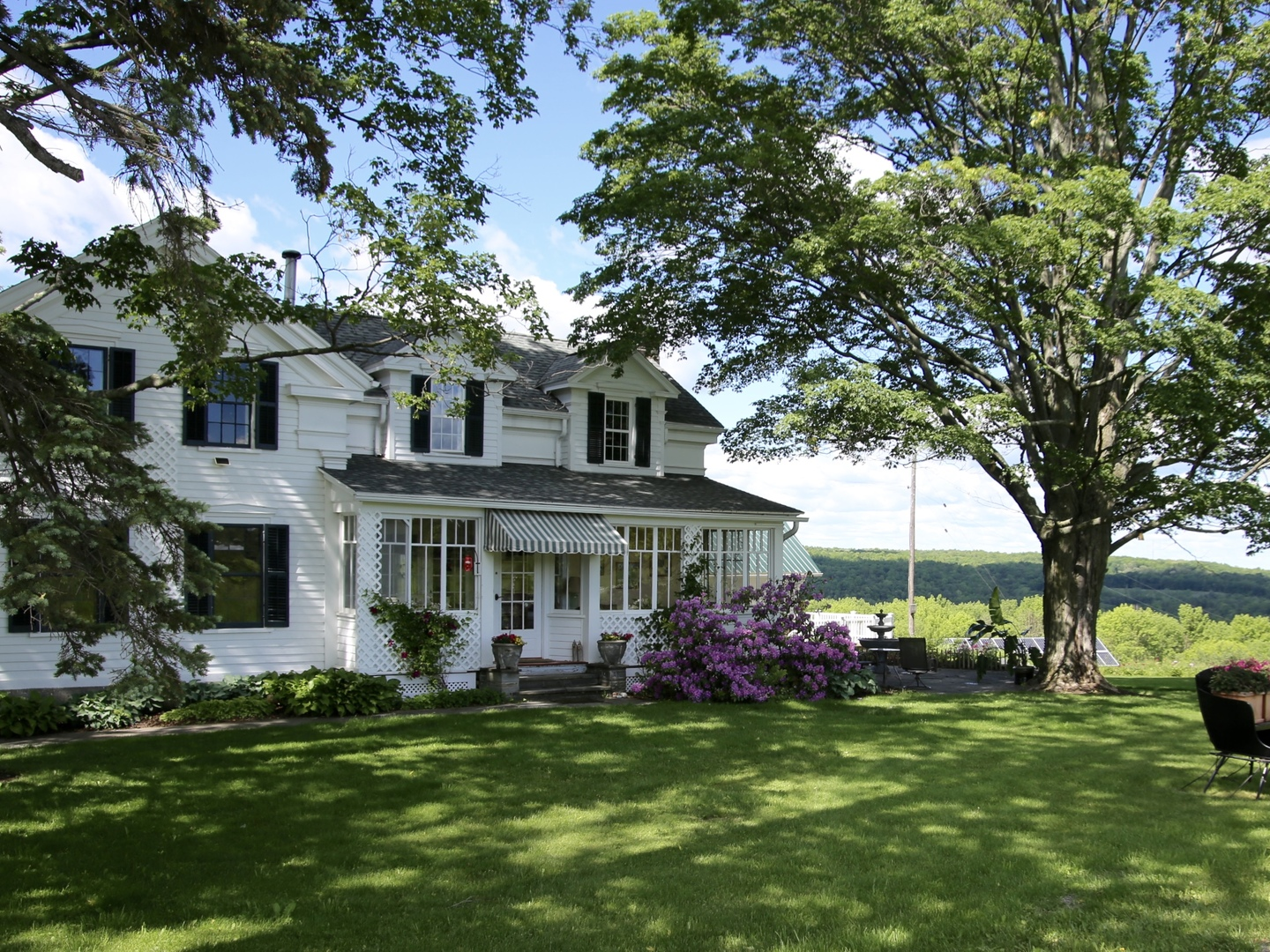 A large lawn in front of a house at Enfield Manor Bed and Breakfast and Vacation Rentals.