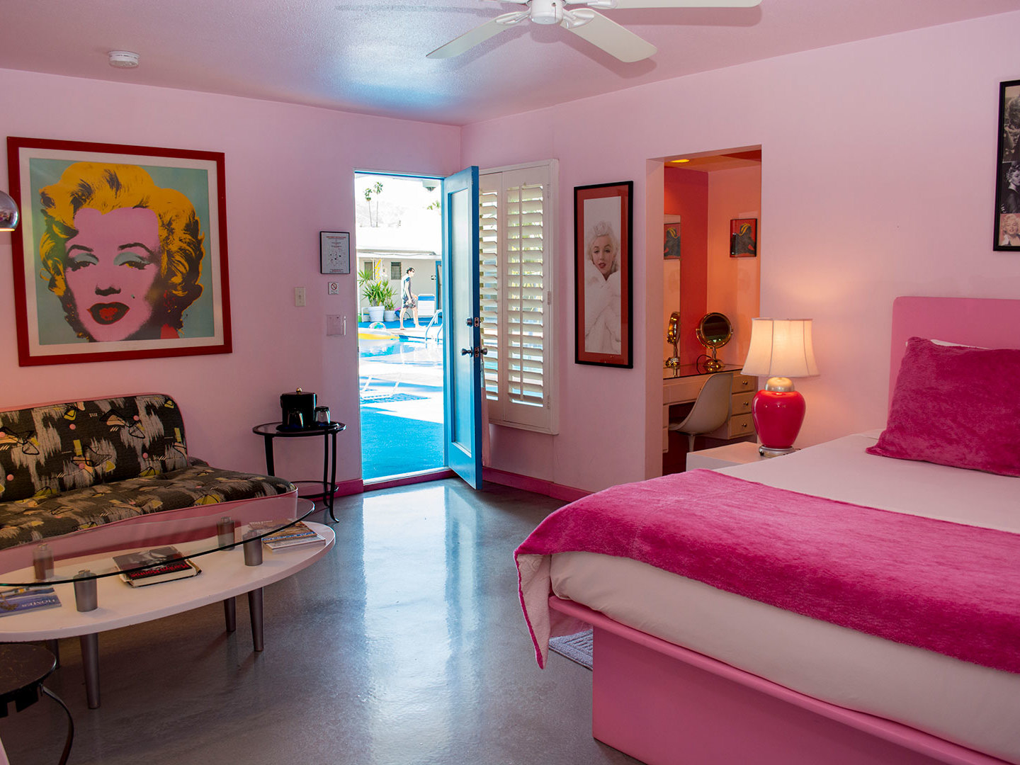 A bedroom with a large red chair in a room at Palm Springs Rendezvous.