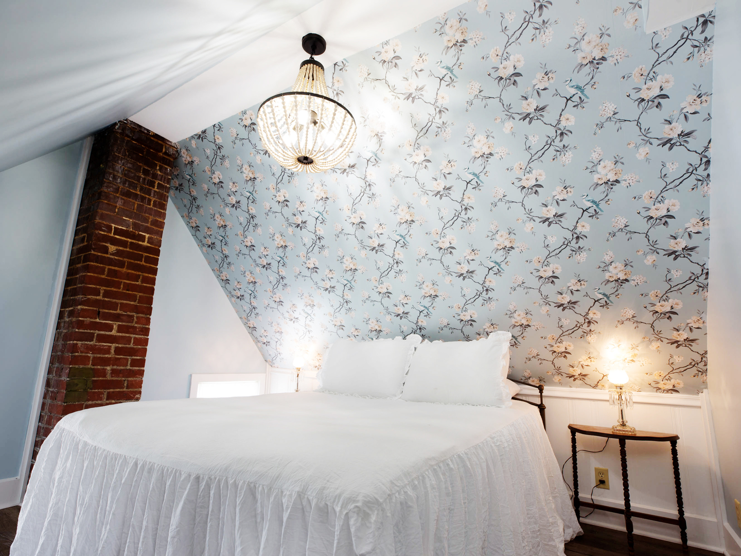 A made bed in a bedroom at The Victorian on Main.