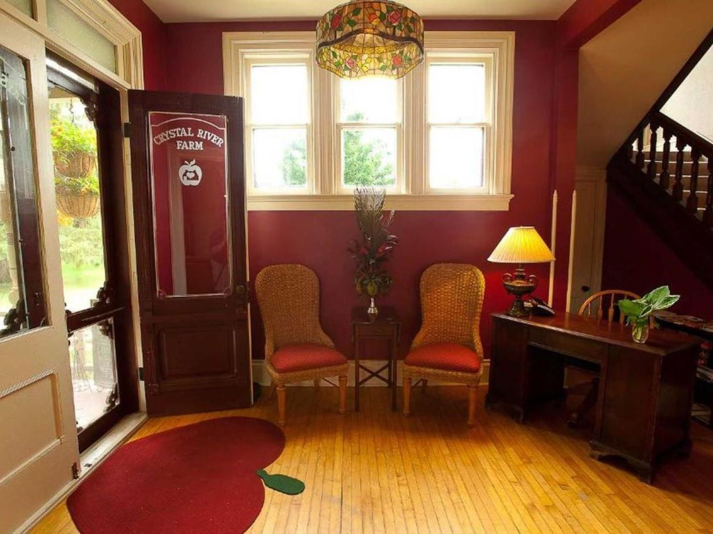 A large red chair in a living room filled with furniture and a window at Apple Tree Lane Bed & Breakfast.