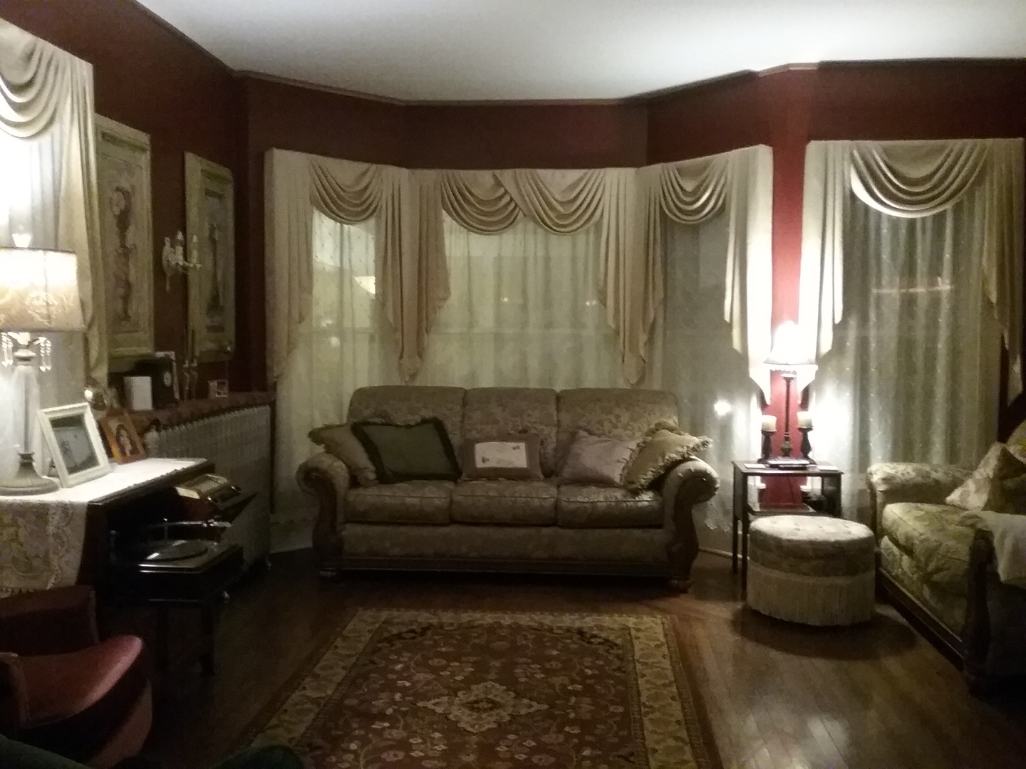 A living room filled with furniture and a large window at Candlelite Inn Bed & Breakfast.
