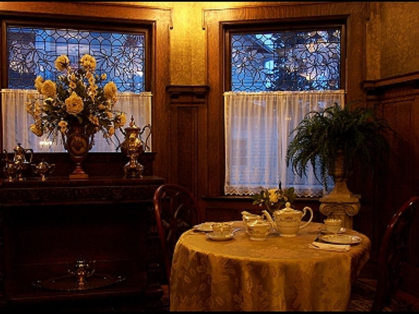 A vase of flowers on a table at Antiquities' Wellington Inn Bed & Breakfast.