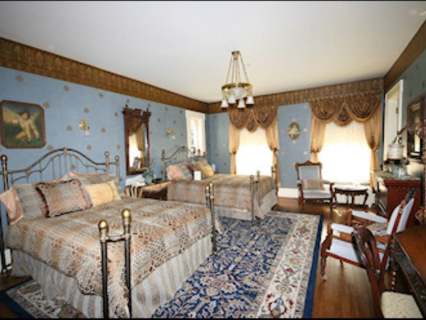 A bedroom with a bed and a chair in a room at Antiquities' Wellington Inn Bed & Breakfast.