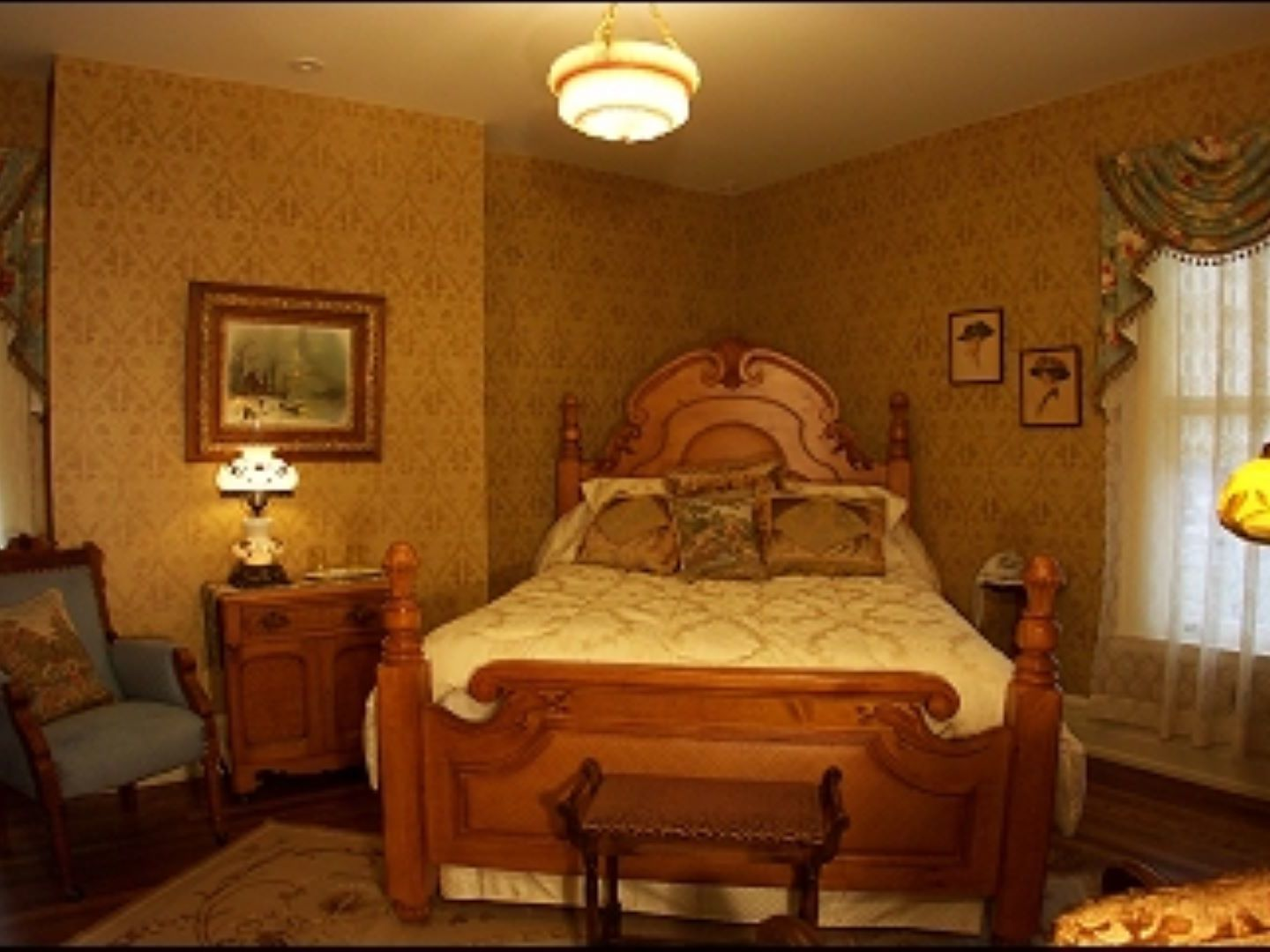 A bedroom with a bed and desk in a room at Antiquities' Wellington Inn Bed & Breakfast.