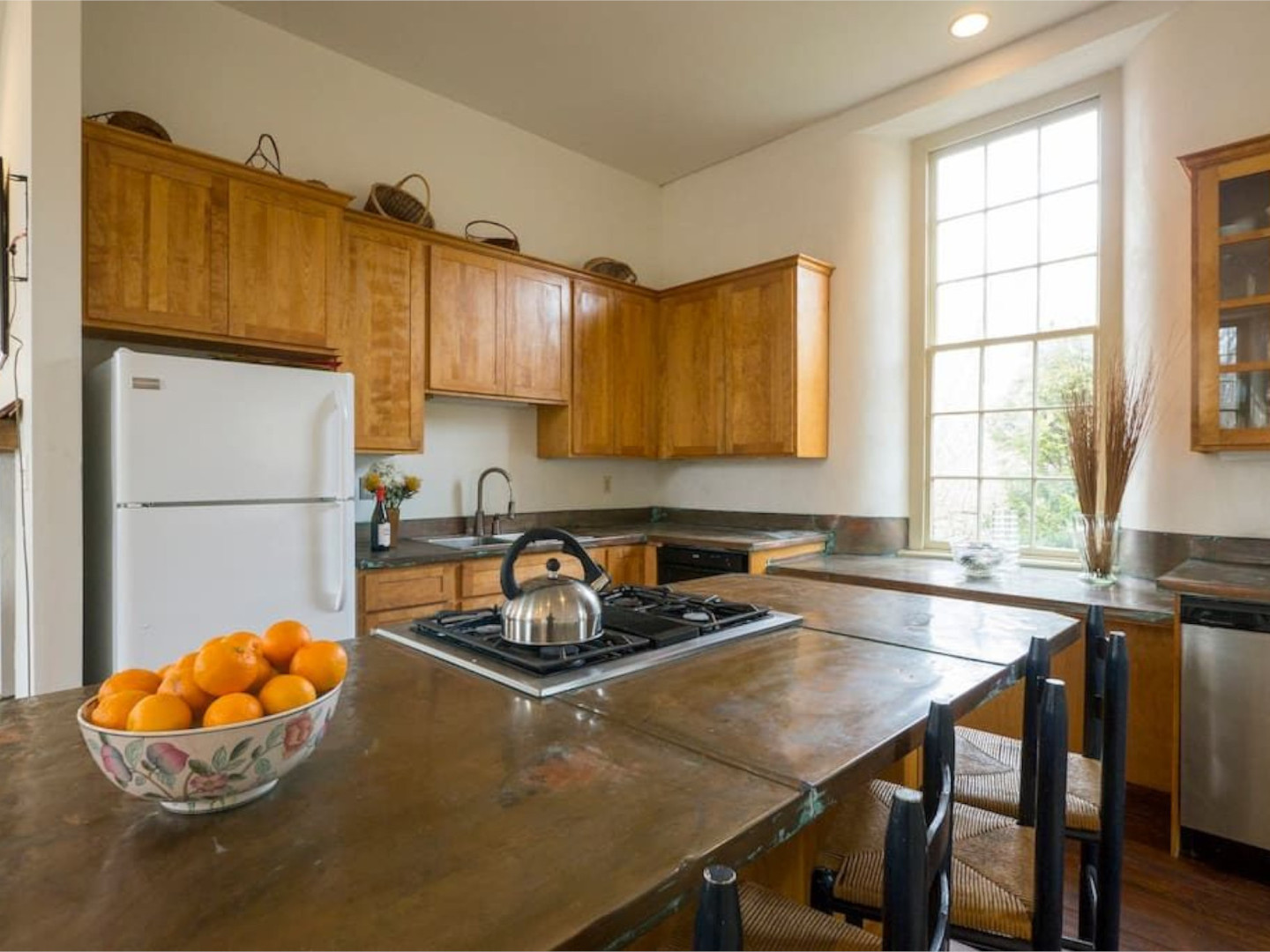 A large kitchen with stainless steel appliances and wooden cabinets at The Buck School Inn.