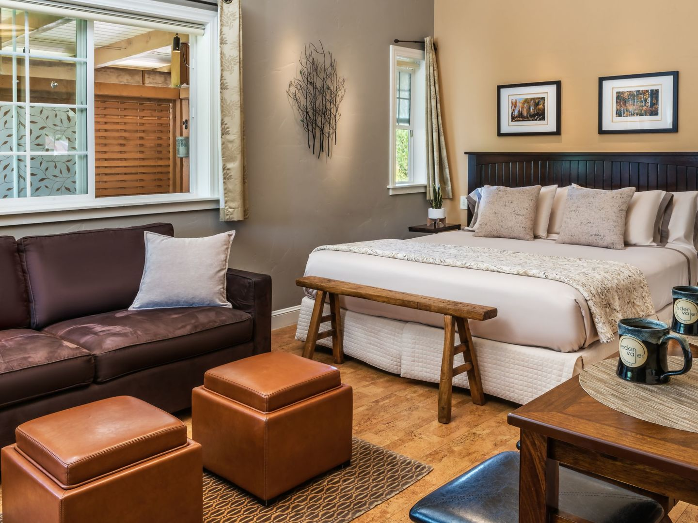 A living room filled with furniture and a large window at Eden Vale Inn.