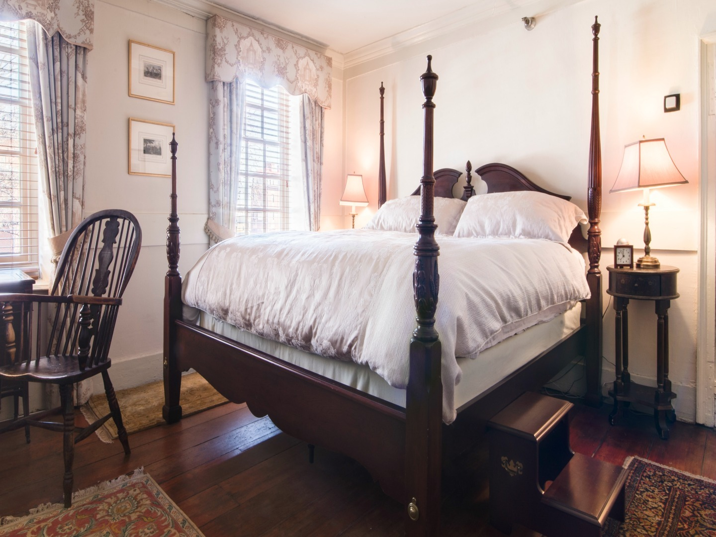 A bedroom with a bed and a chair in a room at Reynolds Tavern.