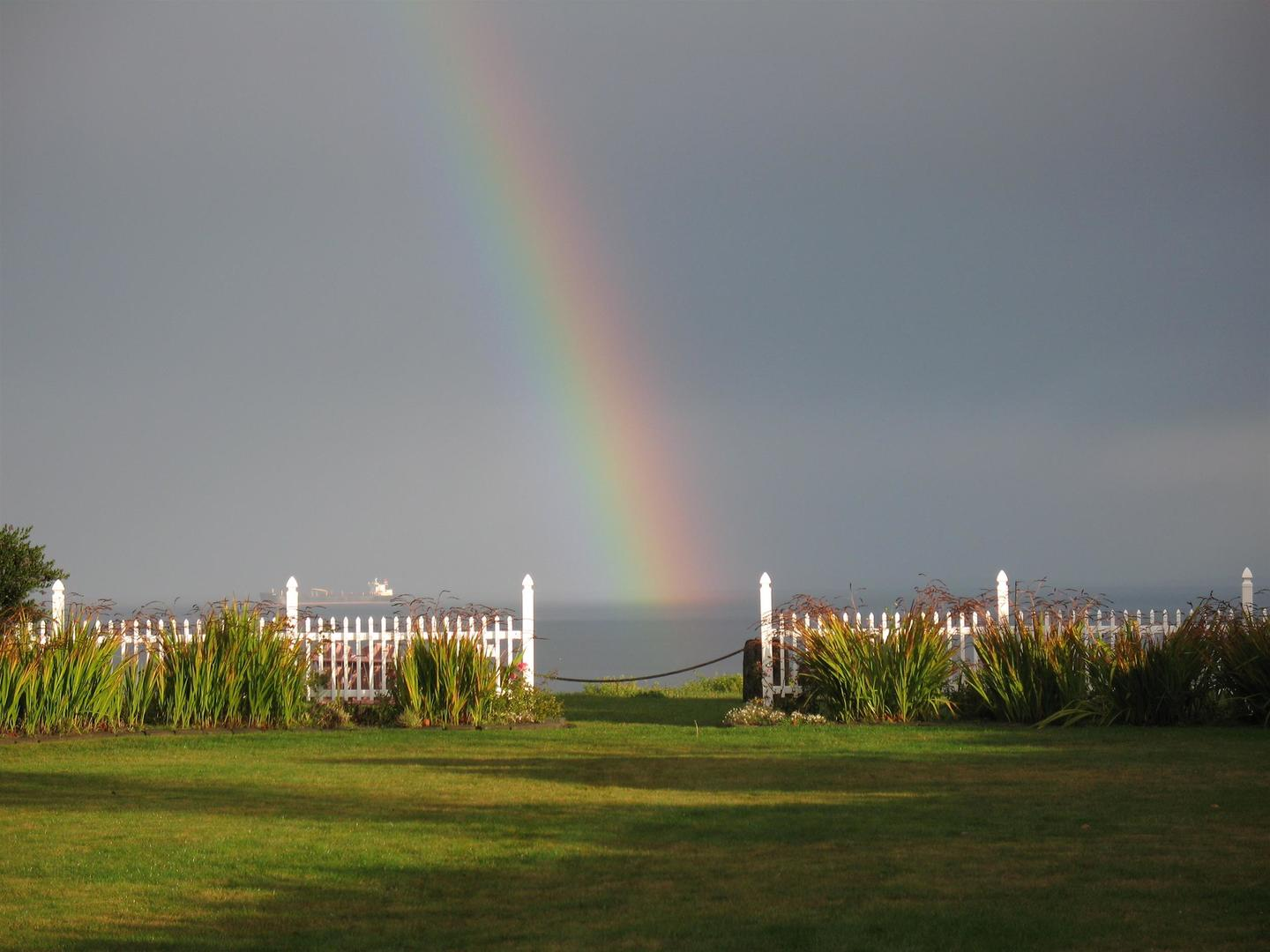 A rainbow over a field of green grass at Sea Cliff Gardens Bed & Breakfast.