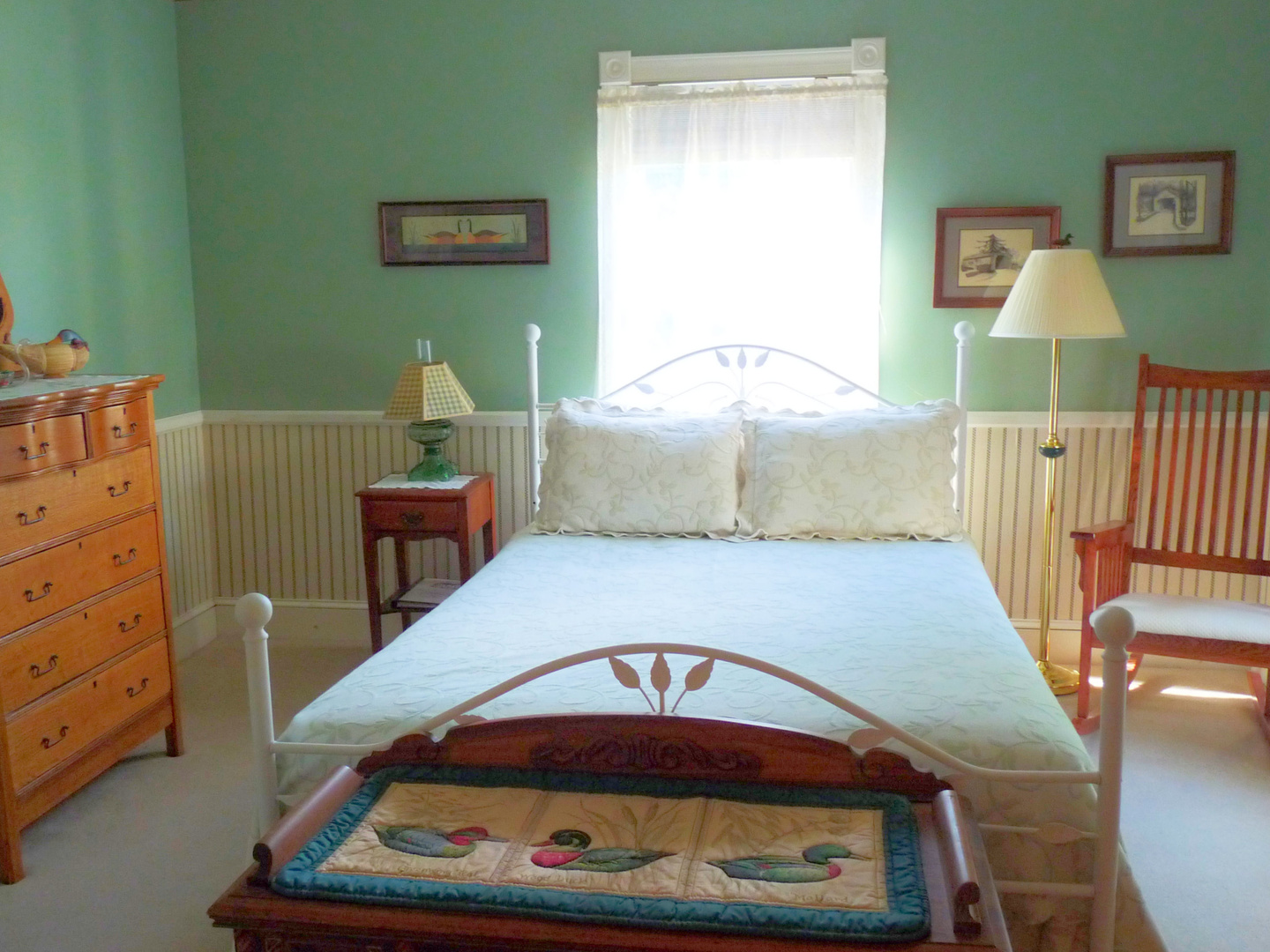 A bedroom with a bed and a chair in a room at J. D. Thompson Inn Bed and Breakfast.