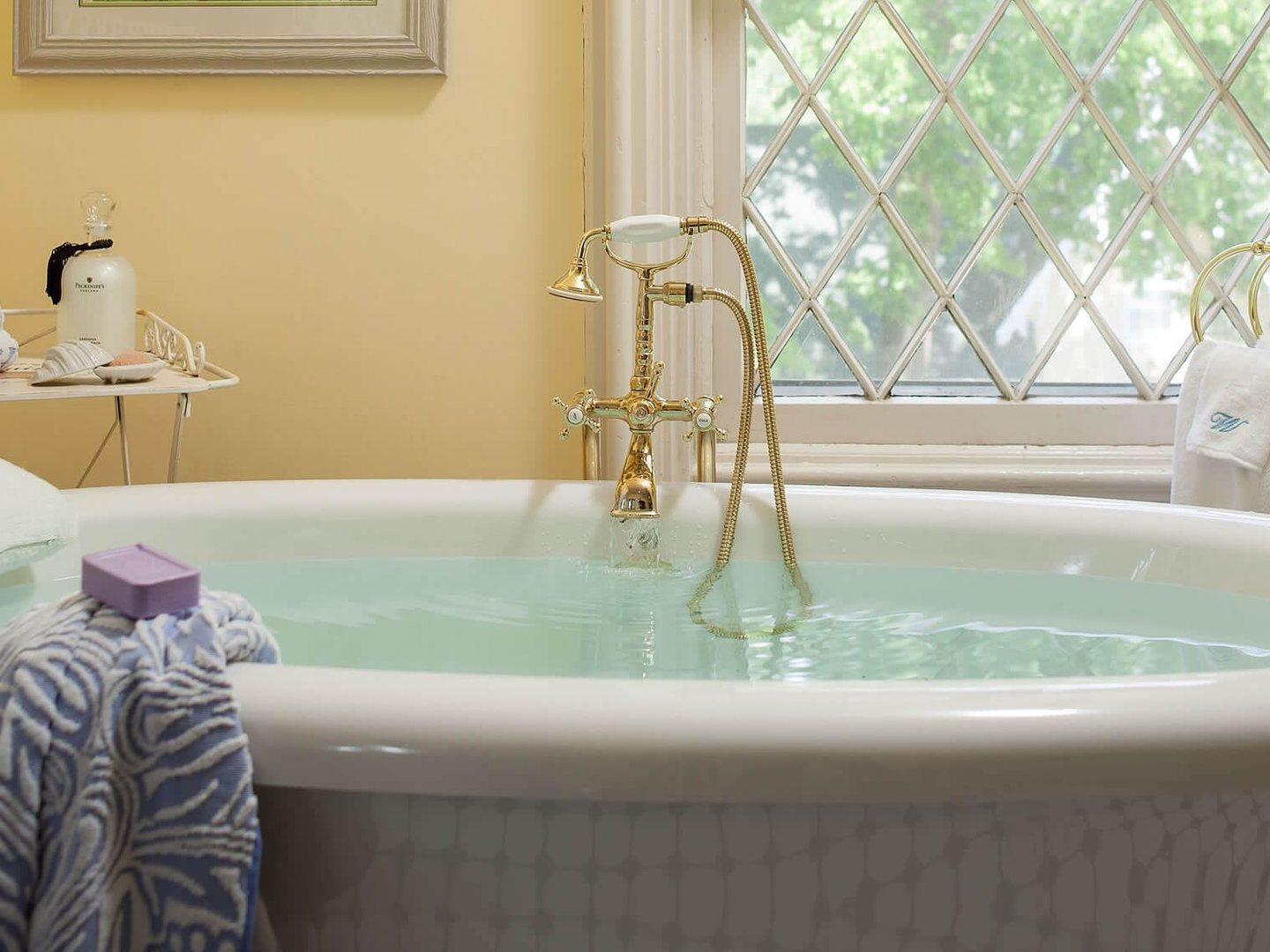 A white tub sitting next to a window at Inn at Woodhaven.