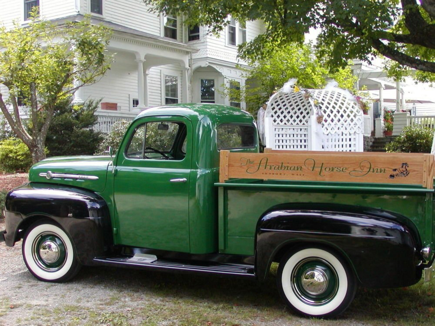 A green truck parked in front of a house at Inn On The Horse Farm.