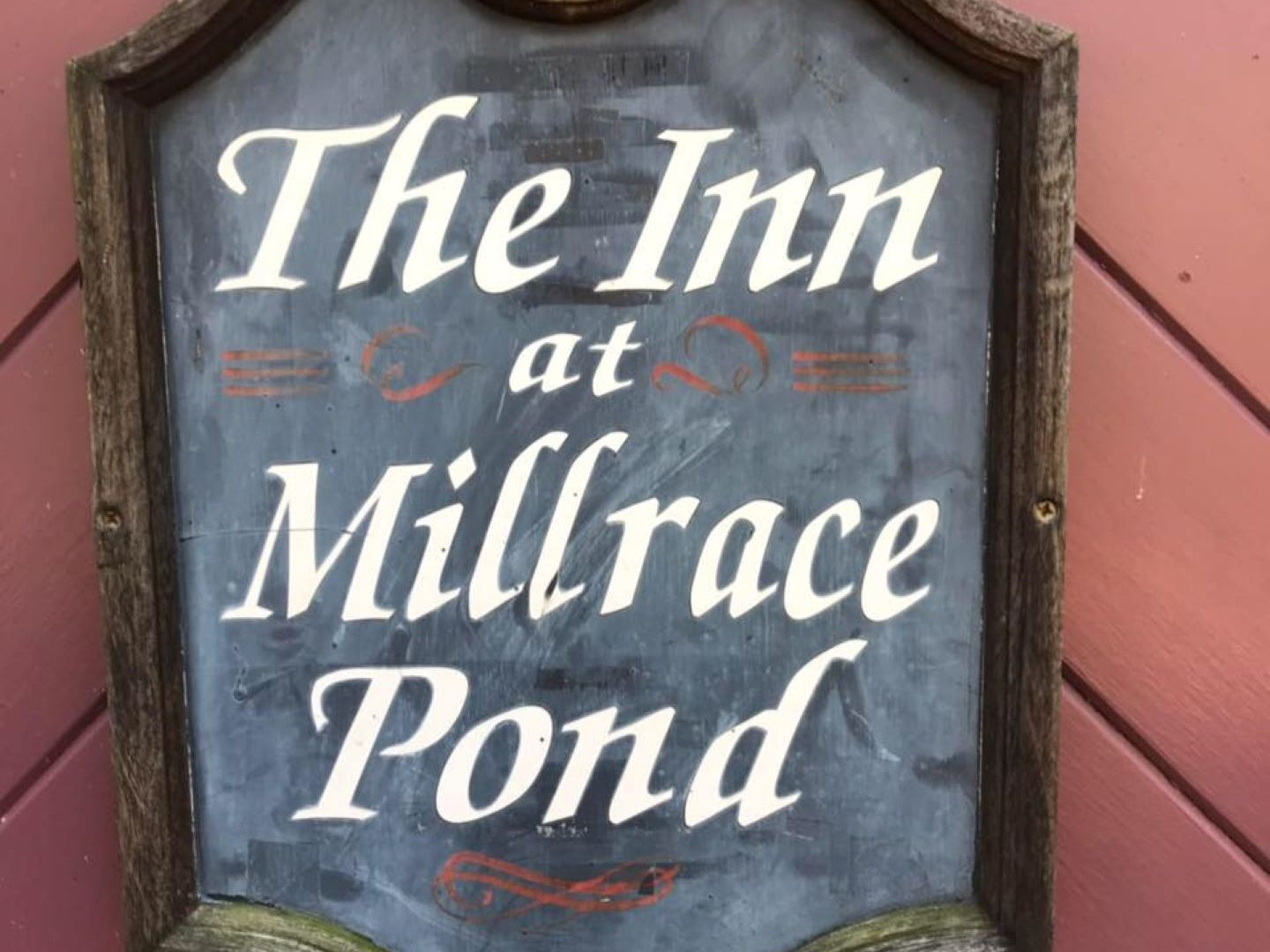 A painted sign hanging on a wall at The Inn at Millrace Pond.