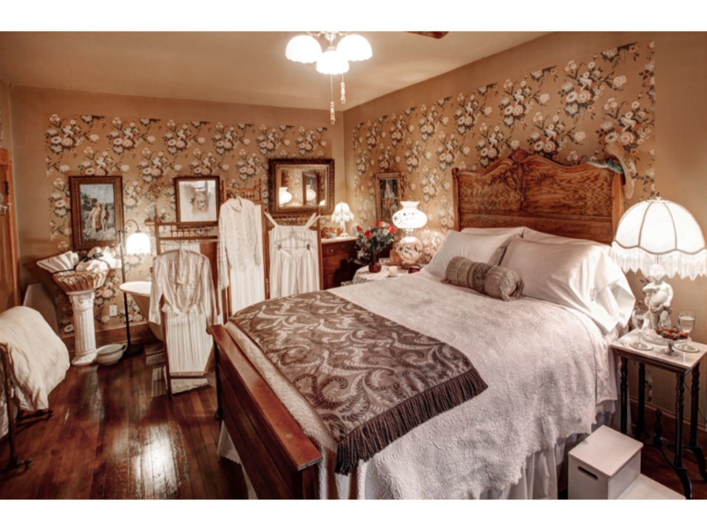 A bedroom with a large bed in a room at The Queen, A Victorian Bed and Breakfast.