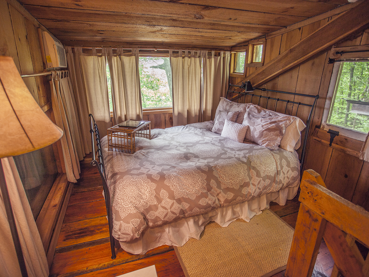 A bedroom with a bed and a chair in a room at Nolichuckey Bluffs Bed & Breakfast Cabins.