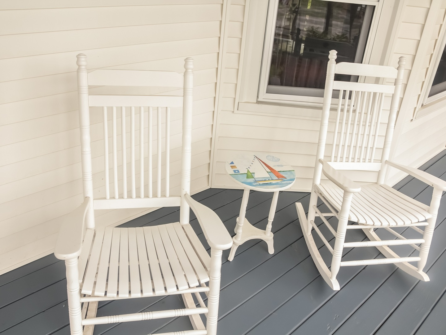 A white bench sitting on top of a wooden chair at Ogunquit Inn & Cottages.