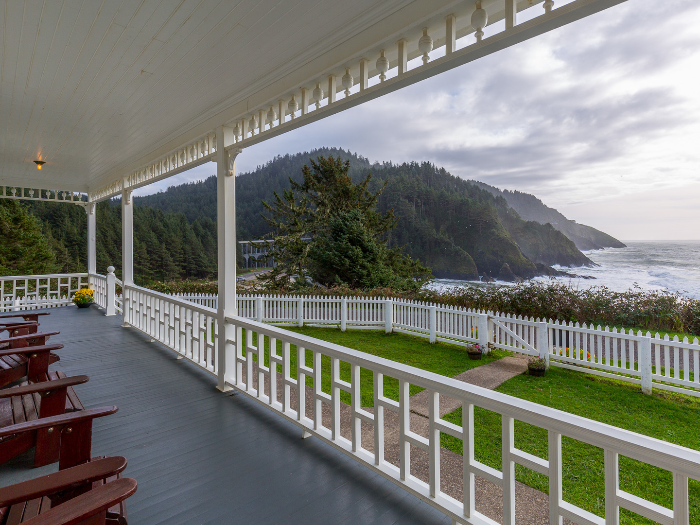 A row of wooden benches sitting on top of a metal fence at Heceta Lighthouse B&B.