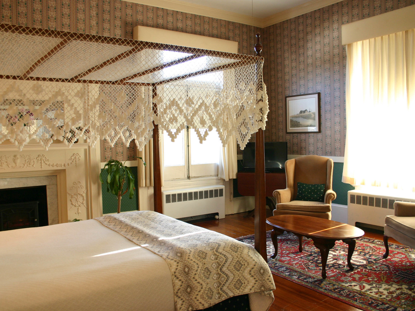 A hotel room with a bed and a fireplace at Wayside Guest House.