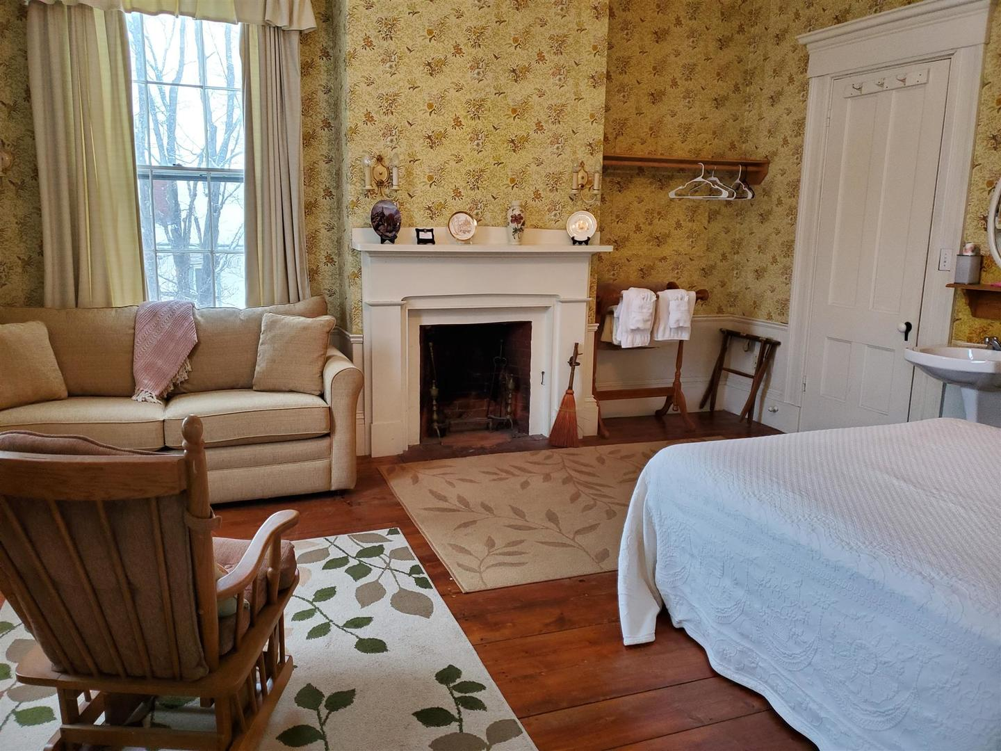 A living room with a bed and a fireplace at The Jeremiah Mason House Bed and Breakfast.