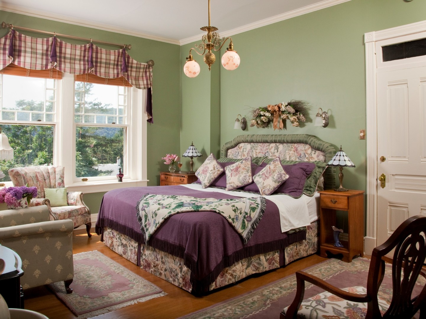 A bedroom with a bed and a chair in a room at B.F. Hiestand House Bed and Breakfast.