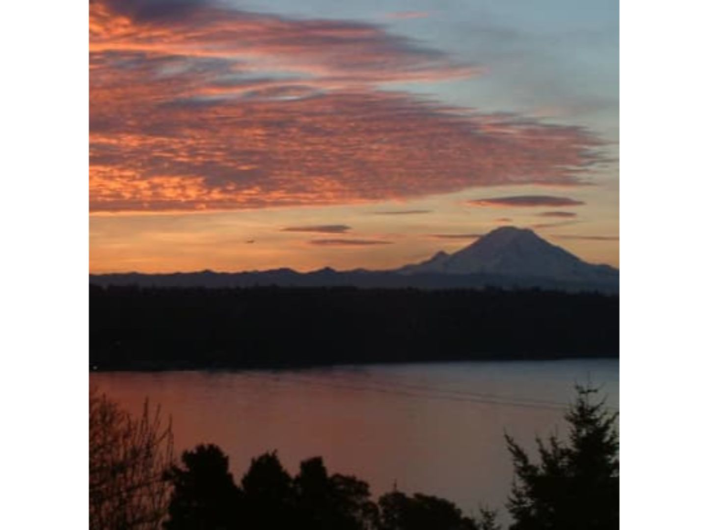 A sunset over a body of water at Three Tree Point Bed & Breakfast.