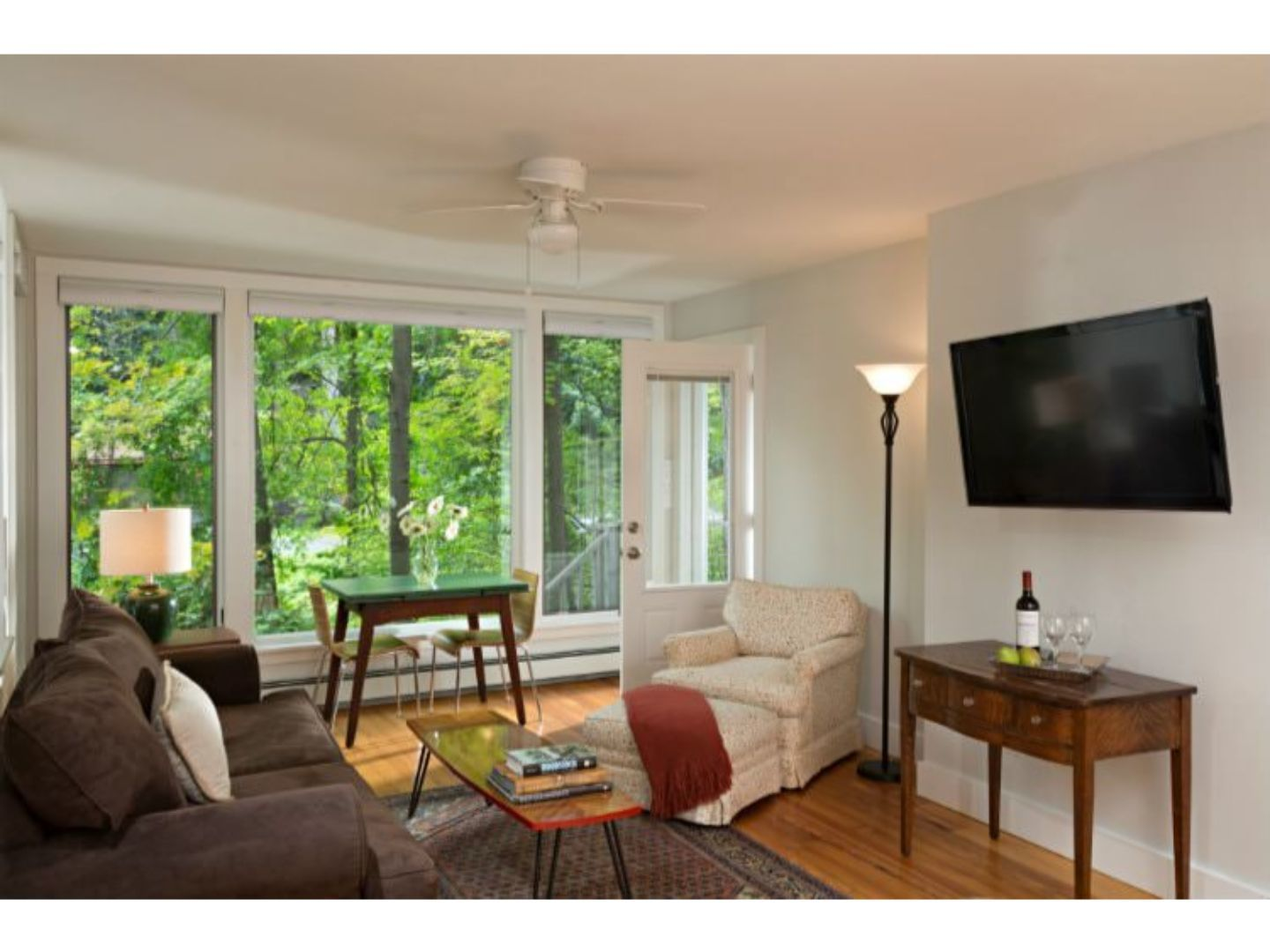 A living room filled with furniture and a large window at The Woodstock Inn on The Millstream.