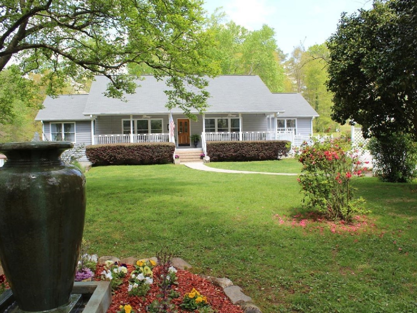 A large lawn in front of a house at Stockbridge Lakes Bed & Breakfast.