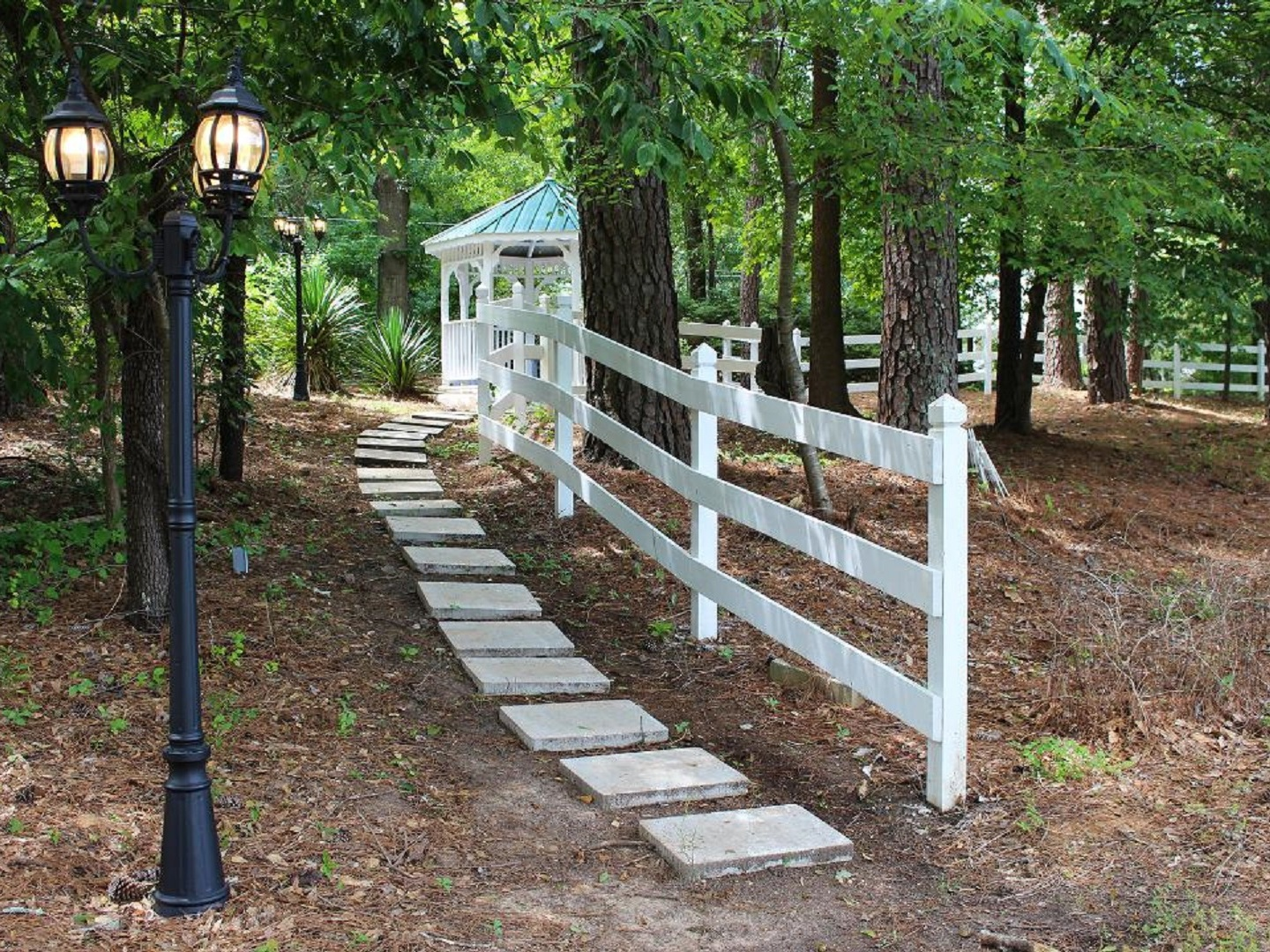A path with trees on the side of a fence at Stockbridge Lakes Bed & Breakfast.