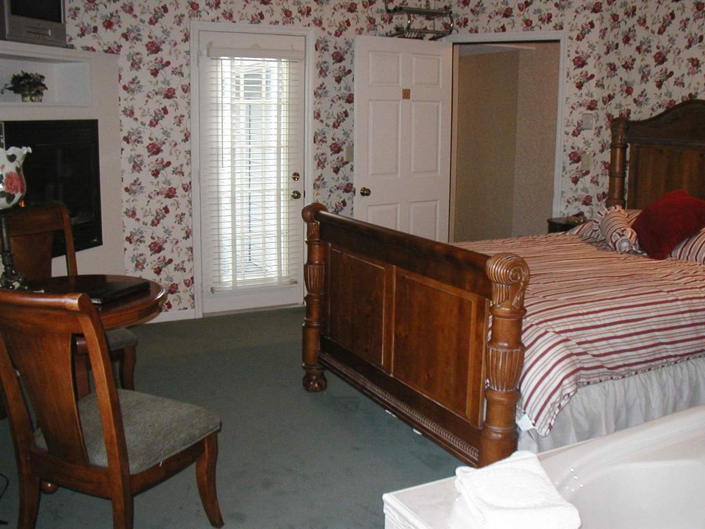 A bedroom with a bed and a chair in a room at Afton House Inn.