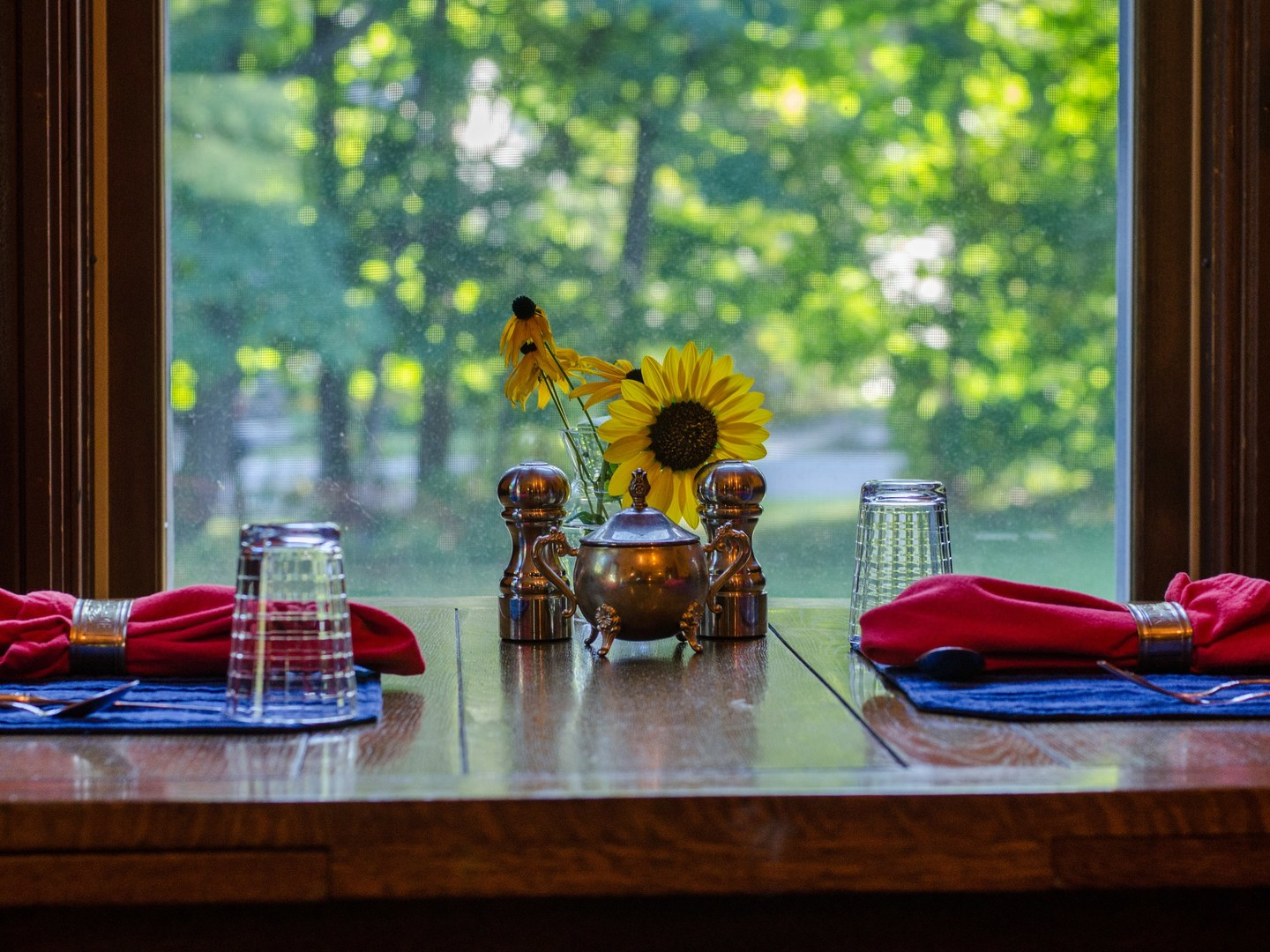 A vase of flowers on a table next to a window at Heart of the Village Inn, Modern Vermont Bed & Breakfast.