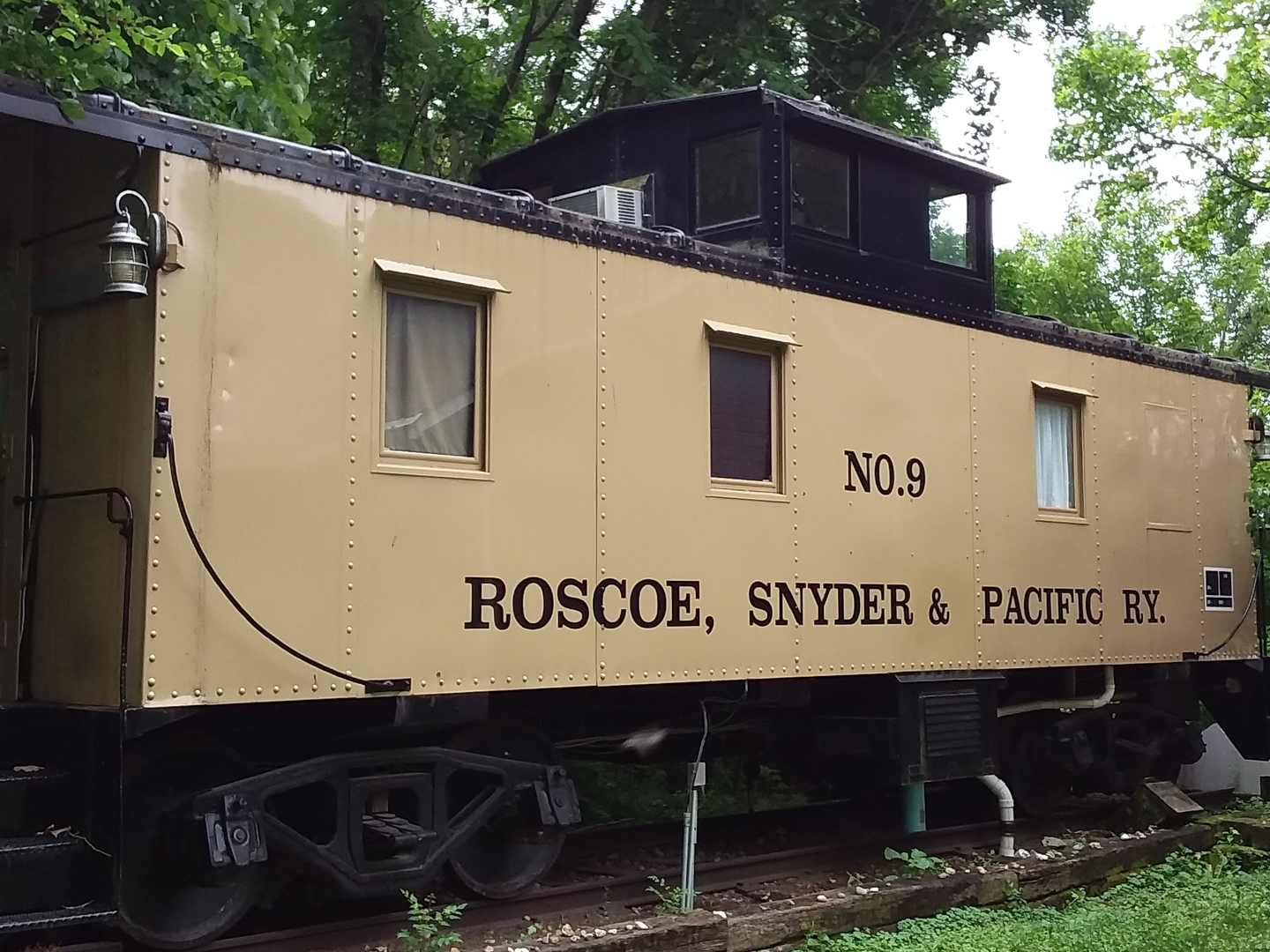 A train is parked on the side at Mason House Inn & Caboose Cottage.