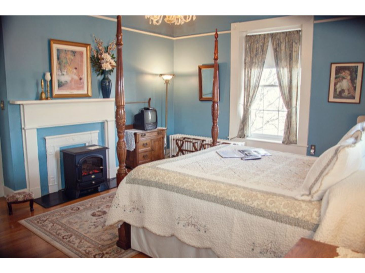 A bedroom with a bed and desk in a room at The Carriage Inn Bed and Breakfast.
