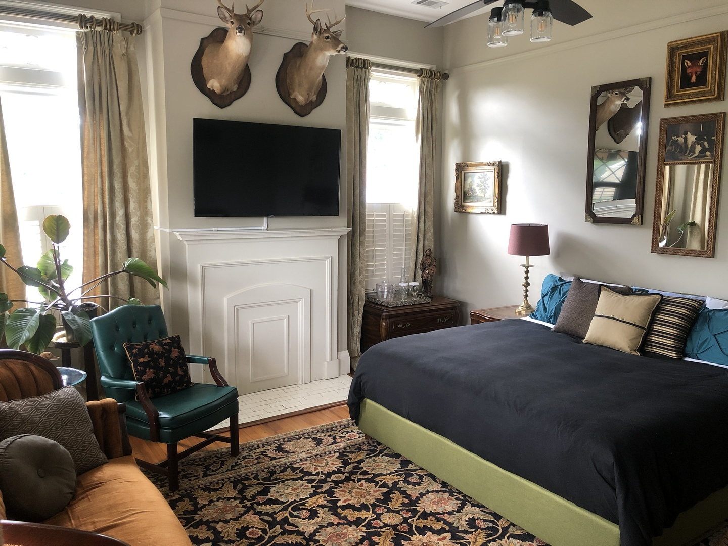 A bedroom with a bed and desk in a room at Heritage House Lodging & Events.