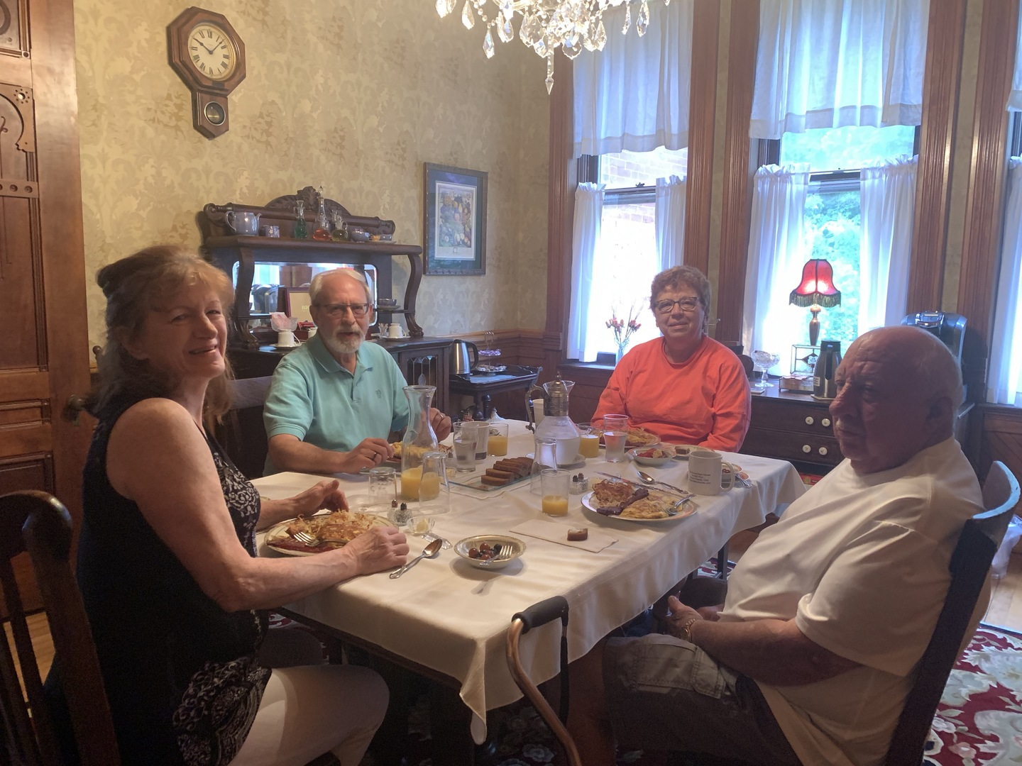 A group of people sitting at a table eating food at The Grand Kerr House.