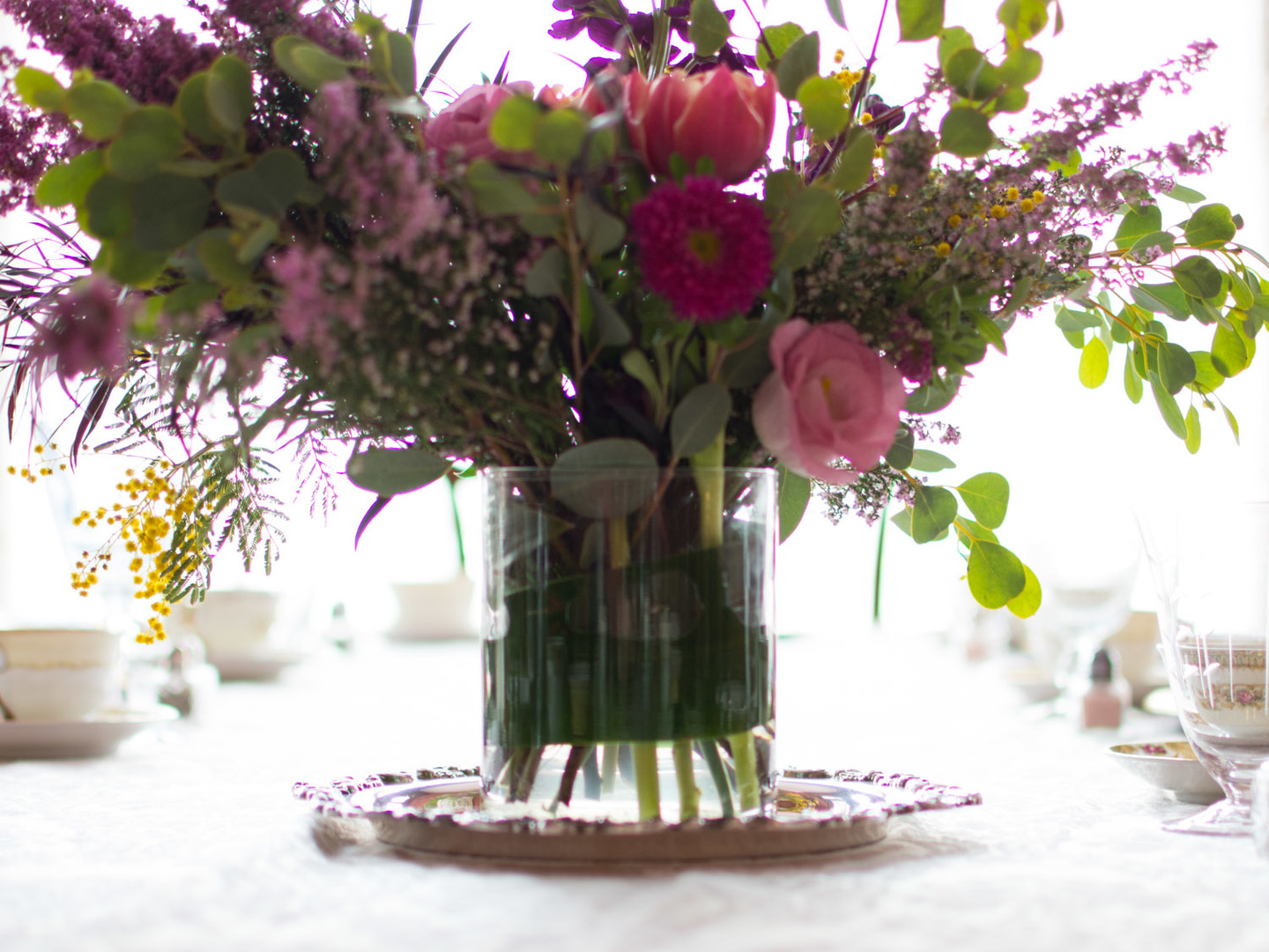 A bouquet of flowers in a vase on a table at Harrison House Bed and Breakfast Lynn Varney.