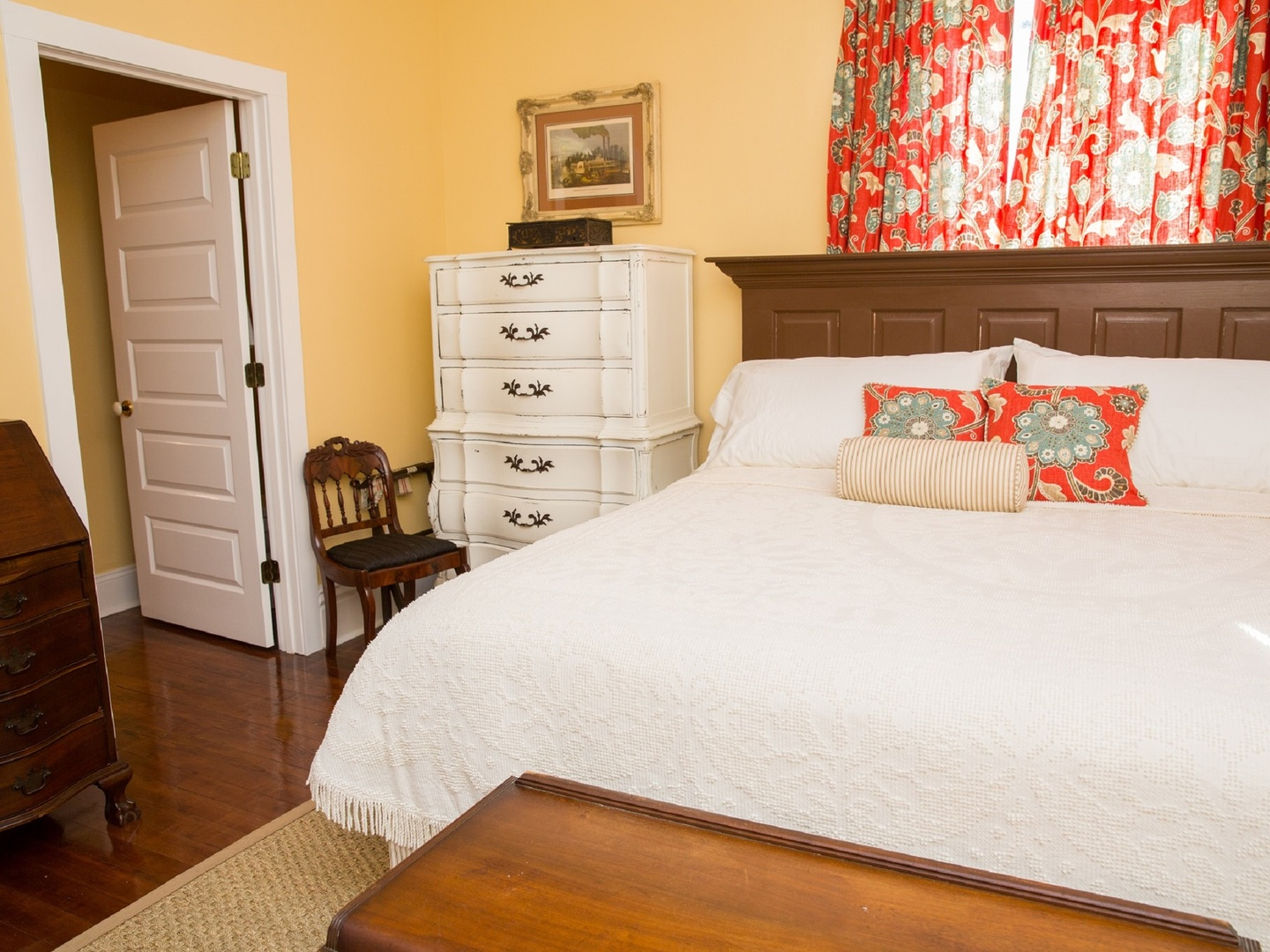 A bedroom with a bed and desk in a room at The Guest House at Gulfport Landing.
