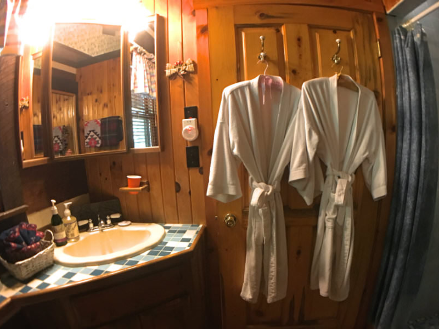 A person standing in front of a mirror posing for the camera at Creekwalk Inn and Cabins.