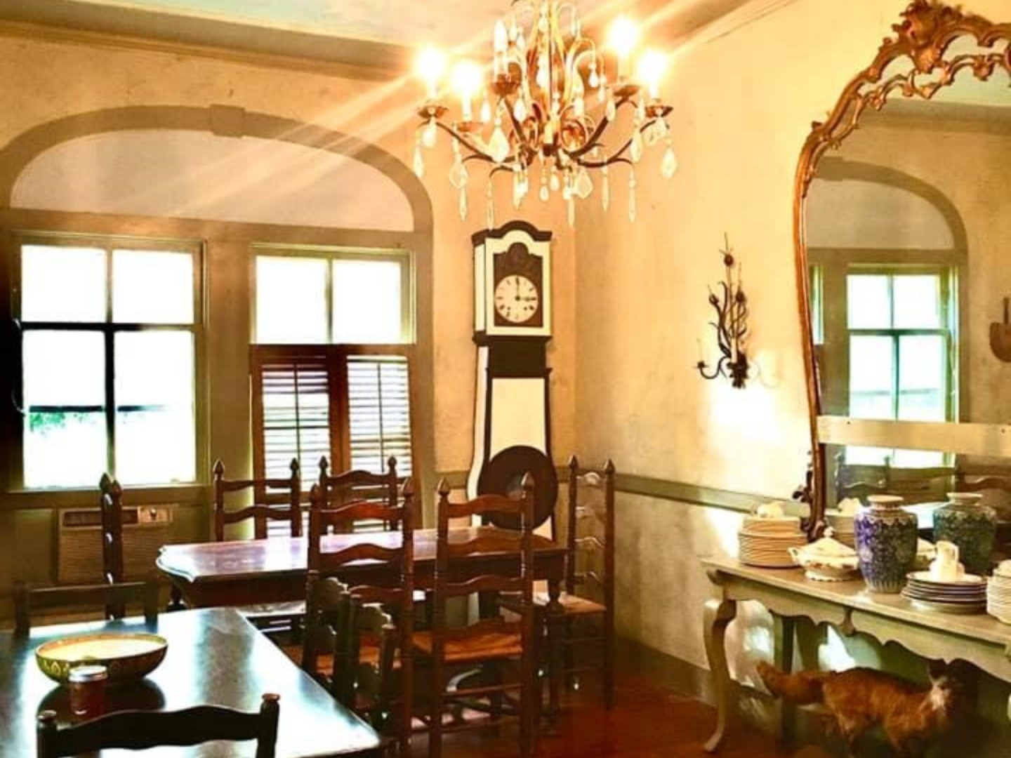 A dining room table in front of a window at John LaFleur's Louisiana Creole Guesthouse.